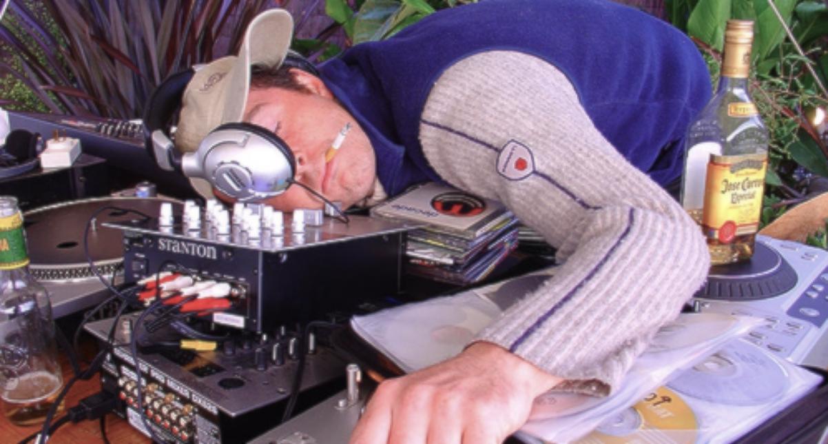 een dj die omvalt van vermoeidheid op zijn dj set, door zijn lifestyle